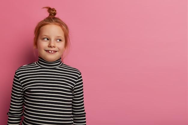 Roodharig meisje kijkt opgewekt opzij, heeft twee uitstekende tanden, draagt een gestreepte trui, is in een goed humeur na thuiskomst van de kleuterschool, poseert binnen op een roze muur. kinderen concept