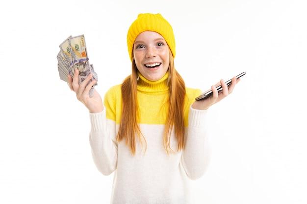 Roodharig meisje met geld met een telefoon in haar handen op wit