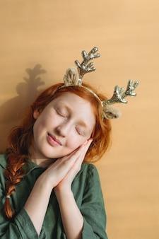 Roodharig meisje met het geweitakken van het kerstmisrendier op haar hoofd