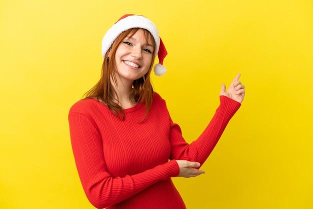 Roodharig meisje met kerstmuts geïsoleerd op een gele achtergrond die de handen naar de zijkant uitstrekt om uit te nodigen om te komen