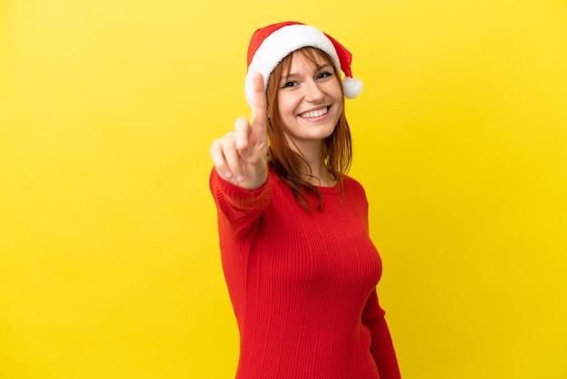 Roodharig meisje met kerstmuts geïsoleerd op een gele achtergrond die een vinger laat zien en optilt