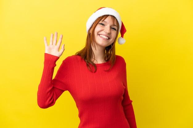 Roodharig meisje met kerstmuts geïsoleerd op gele achtergrond saluerend met de hand met gelukkige uitdrukking