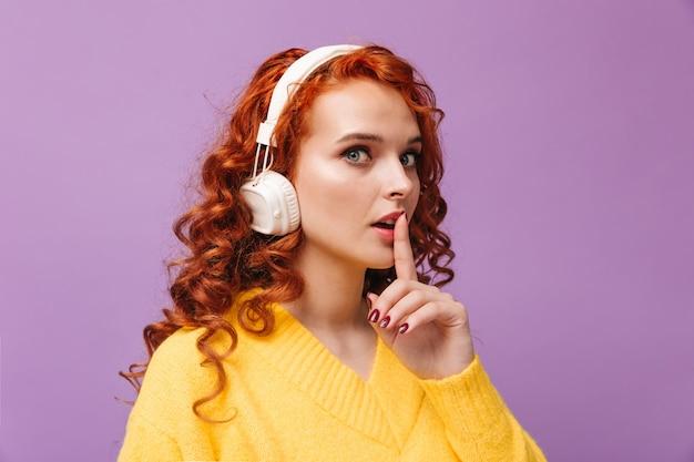 Roodharig meisje met koptelefoon kijkt naar voren en legt haar vinger op haar mond en vraagt om geheim te houden