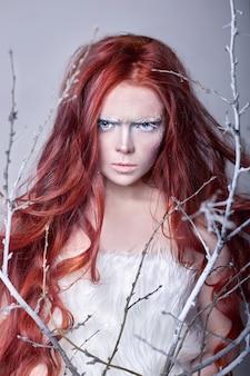 Roodharig meisje met lang haar, een gezicht bedekt met sneeuw met vorst. witte wenkbrauwen en wimpers in de vorst, een boomtak bedekt met sneeuw. sneeuwkoningin en winter. winter make-up vrouw gezicht, rood hoofd