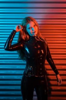 Roodharig meisje met latex, een zwarte top en strakke broek, op een metalen achtergrond verlicht met rode en blauwe led's, poseerde kijkend naar de camera