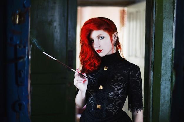 Roodharig meisje met rode lippen in een donkere kamer, een vrouw houdt het mondstuk met een sigaret in zijn hand