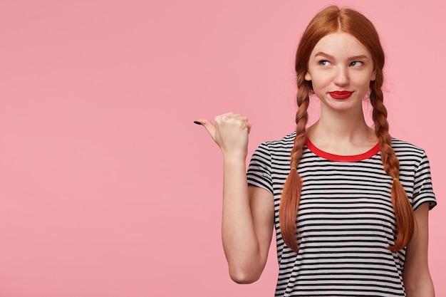 Roodharig meisje met twee vlechten wijzend met duim naar links op lege kopie ruimte en kijkt daar mysterieus intrigerend, speels lachend, bedacht iets, op roze muur
