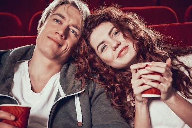 Roodharig meisje met vriendje kijken naar film in de bioscoop.