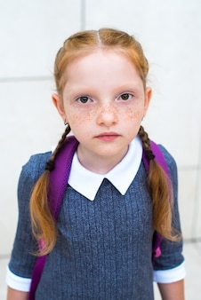 Roodharig meisje, schoolmeisje ziet er verdrietig uit. sproeten en oranje vlechten.