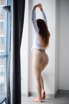 Roodharig meisje staat op blote voeten bij het raam thuis