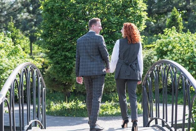 Roodharig paar. man en vrouw in formele kleding lopen op de brug in de natuur