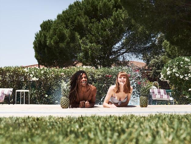 Roodharig russisch meisje en afro-amerikaanse jongen met dreadlocks die water spatten en spatten aan de rand van het zwembad.