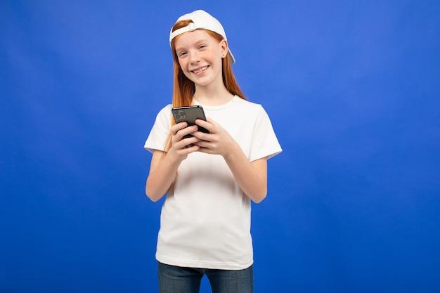 Roodharig tienermeisje in een wit t-shirt communiceert in instant messengers met een smartphone in de hand blauw