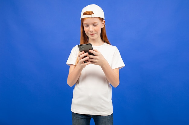 Roodharig tienermeisje in een wit t-shirt communiceert in instant messengers