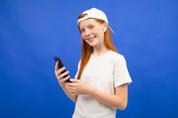 Roodharig tienermeisje in een wit t-shirt en een baseballpet luistert naar muziek met behulp van een draadloze hoofdtelefoon met een smartphone in de hand blauw