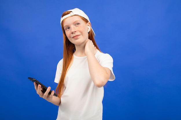 Roodharig tienermeisje in een wit t-shirt luistert naar muziek met behulp van draadloze hoofdtelefoons met een smartphone in de hand blauw