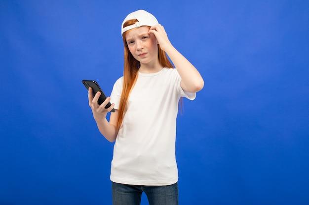 Roodharig tienermeisje in een wit t-shirt met nadenkende telefoons houdend een smartphone in haar handblauw
