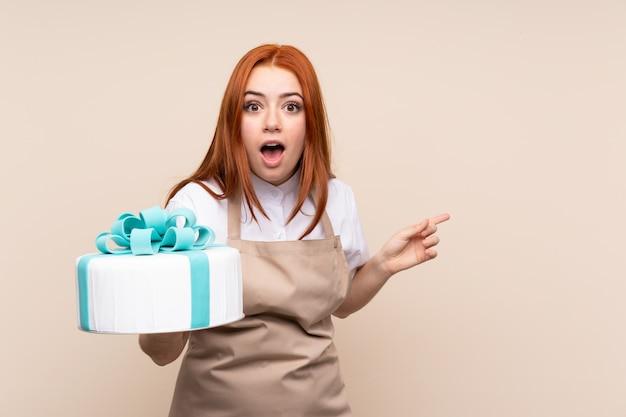 Roodharig tienermeisje met een grote cake over geïsoleerde muur verrast en wijzende vinger aan de kant