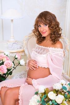 Roodharig zwanger meisje zittend op een stoel en buik knuffelen met liefde Premium Foto