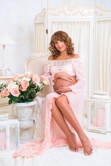 Roodharig zwanger meisje zittend op een stoel en buik knuffelen met liefde