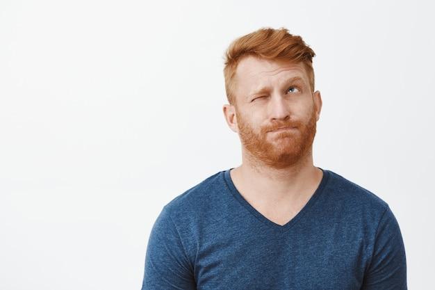 Roodharige aantrekkelijke man met borstelharen in casual blauw t-shirt, lippen tuitend hmm-geluid maken, één oog sluiten en opzoeken, nadenken of beslissingen nemen
