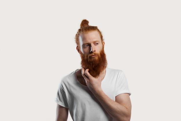Roodharige aantrekkelijke man probeert een nieuw idee te onthouden en krabt aan een rode baard en kijkt weg met een sceptische uitdrukking