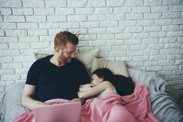 Roodharige alleenstaande vader werkt met laptop.