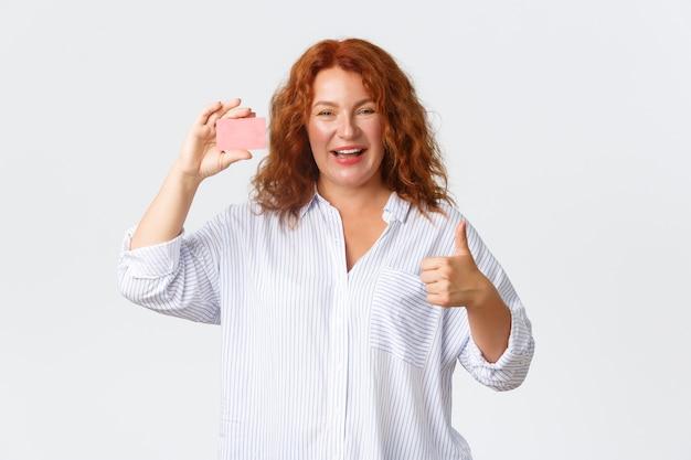 Roodharige bankklant van middelbare leeftijd, vrouwelijke ondernemer raadt bankieren aan, creditcard toont en thumbs-up tevreden