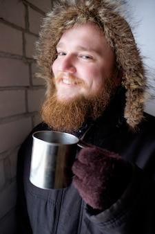 Roodharige bebaarde man in polaire jas met kop warme koffie of thee en lachend