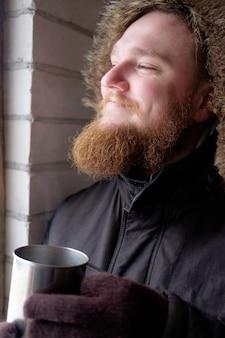 Roodharige bebaarde man in polaire jas met kop warme koffie of thee
