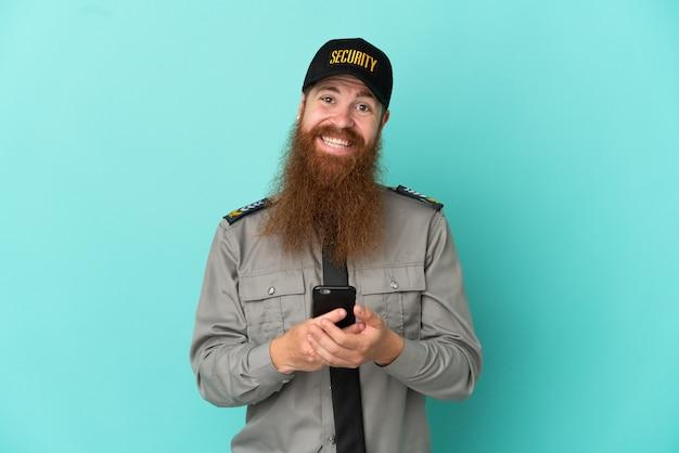 Roodharige beveiligingsman geïsoleerd op een witte achtergrond die een bericht verzendt met de mobiel