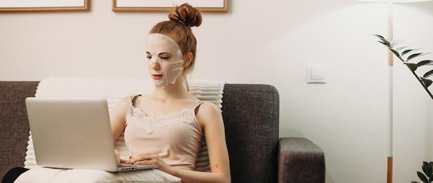 Roodharige blanke dame zittend op de bank en werkt op de computer terwijl ze een papieren speciaal masker voor de huid van het gezicht draagt