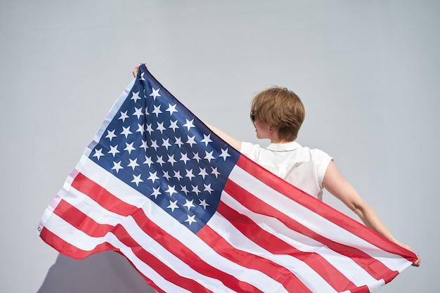 Roodharige blanke meisje houdt zwaaide door de wind usa vlag achter haar rug