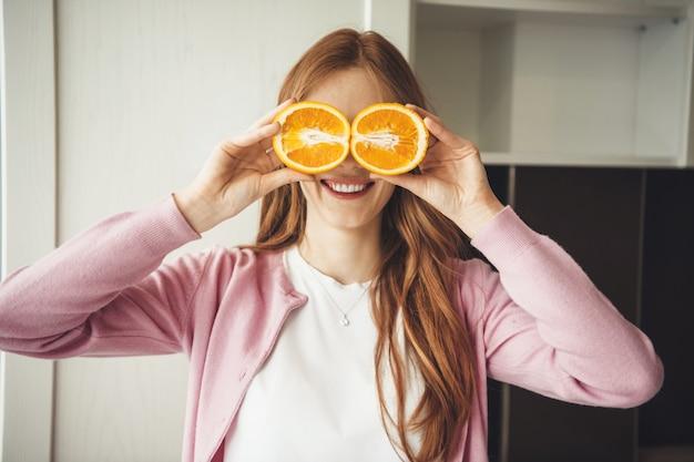 Roodharige blanke vrouw die lacht terwijl haar ogen bedekken met sinaasappels in de keuken