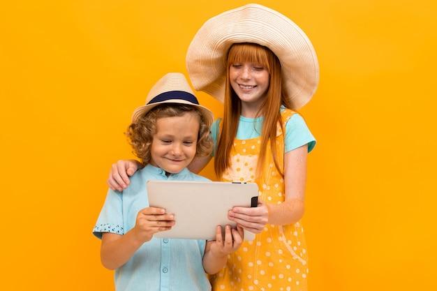 Roodharige broer en zus in zomerhoeden boeken kaartjes op een tablet op een gele achtergrond.