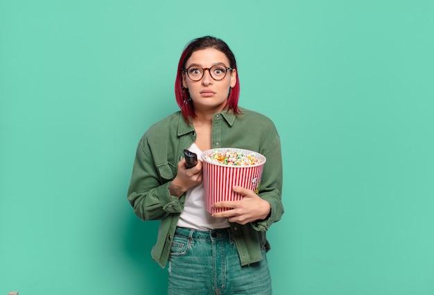 Roodharige coole vrouw met popcorns en een tv-afstandsbediening tv