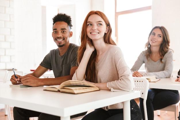 Roodharige dame student zit in de klas in de buurt van afrikaanse vriend man