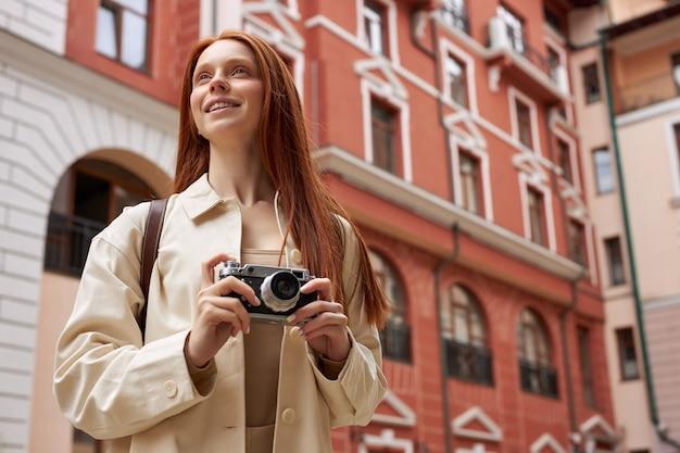 Roodharige fotograaf vrouw met retro camera in handen kijken naar stedelijke oude architectuur