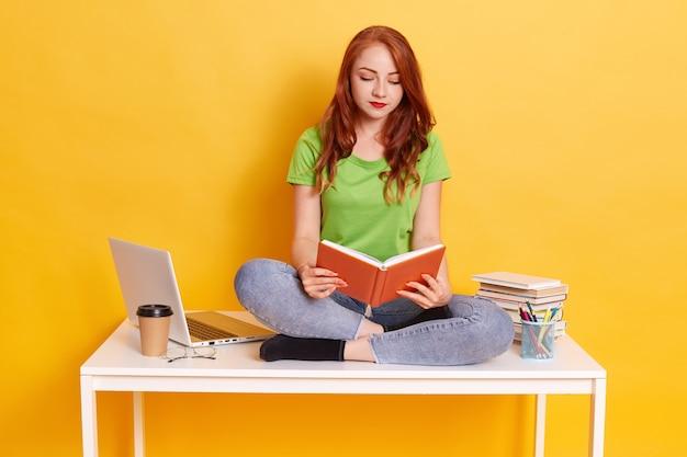 Roodharige geconcentreerde vrouw draagt groene t-shirt en spijkerbroek, houdt boeken in handen en leest, student zittend op tafel met gekruiste benen, dame omringd met laptop, pennen