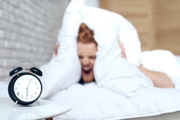 Roodharige geïrriteerde man wordt wakker van luide alarmbel.