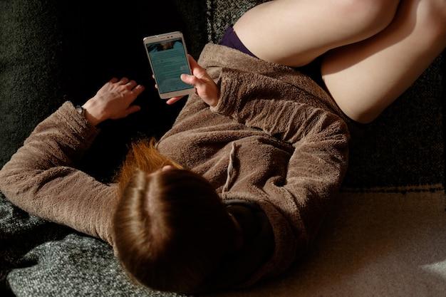 Roodharige gember meisje in hoodie kijken naar app op smartphone, zittend op de bank