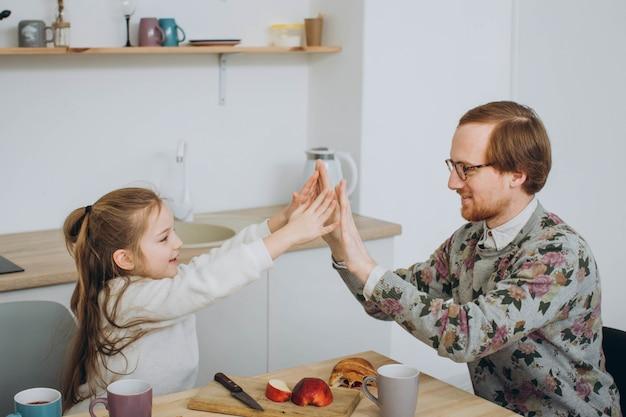 Roodharige hipster vader en dochter hebben plezier in de keuken.