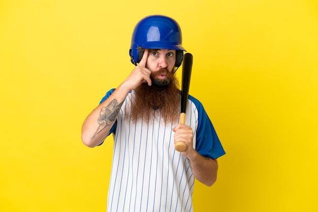 Roodharige honkbalspeler man met helm en vleermuis geïsoleerd op gele achtergrond denken een idee