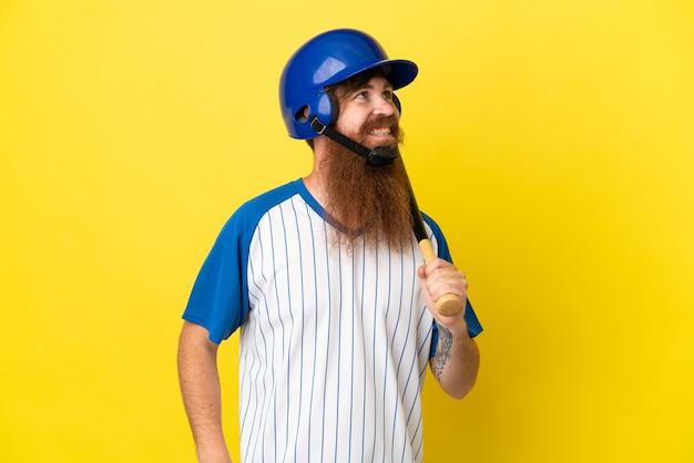 Roodharige honkbalspeler man met helm en vleermuis geïsoleerd op gele achtergrond die een idee denkt terwijl hij omhoog kijkt