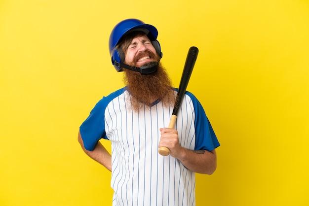 Roodharige honkbalspeler man met helm en vleermuis geïsoleerd op gele achtergrond die lijdt aan rugpijn omdat hij moeite heeft gedaan