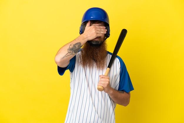 Roodharige honkbalspeler man met helm en vleermuis geïsoleerd op gele achtergrond die ogen bedekt door handen. wil je iets niet zien
