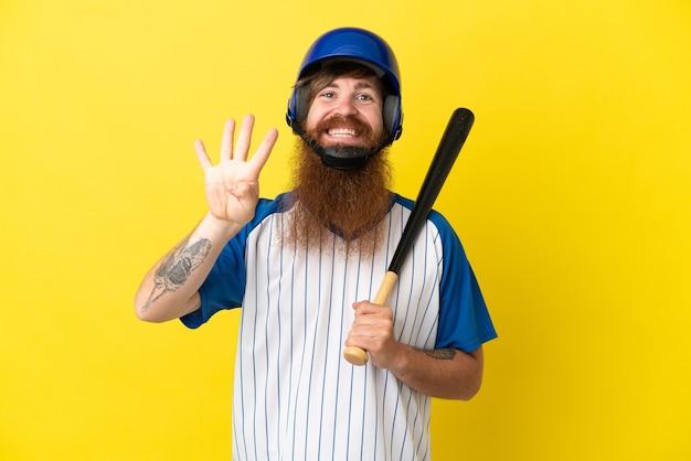 Roodharige honkbalspeler man met helm en vleermuis geïsoleerd op gele achtergrond gelukkig en vier tellen met vingers