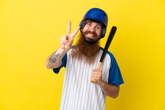 Roodharige honkbalspeler man met helm en vleermuis geïsoleerd op gele achtergrond glimlachend en overwinningsteken tonen