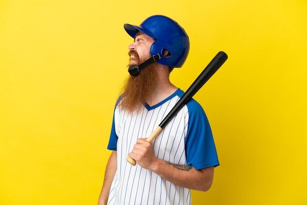 Roodharige honkbalspeler man met helm en vleermuis geïsoleerd op gele achtergrond lachen in laterale positie