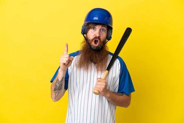 Roodharige honkbalspeler man met helm en vleermuis geïsoleerd op gele achtergrond met de bedoeling de oplossing te realiseren terwijl hij een vinger optilt